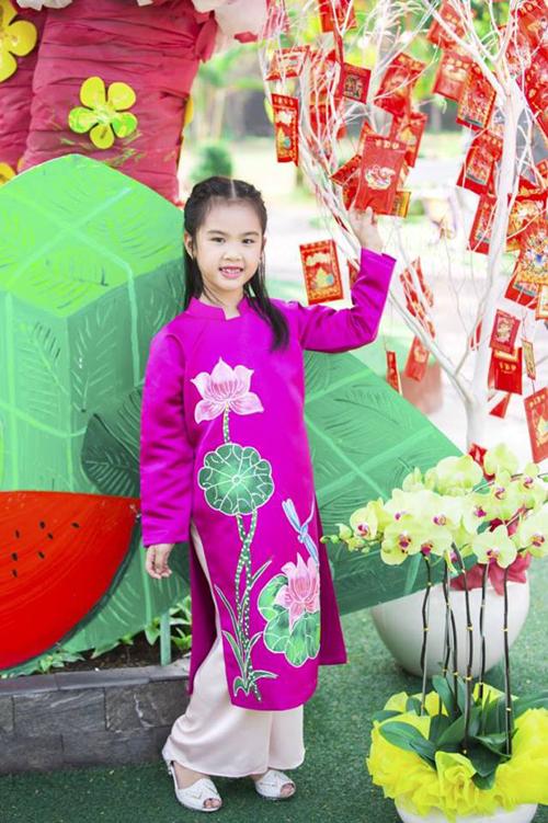 Bé Ngọc Anh làm duyên với áo dài vẽ hoa sen.