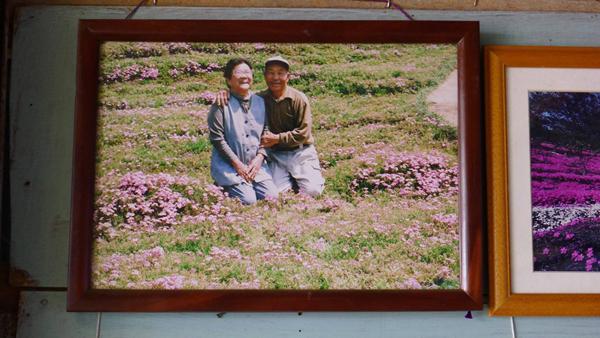 Cặp vợ chồng già chụp ảnh bên vườn hoa.