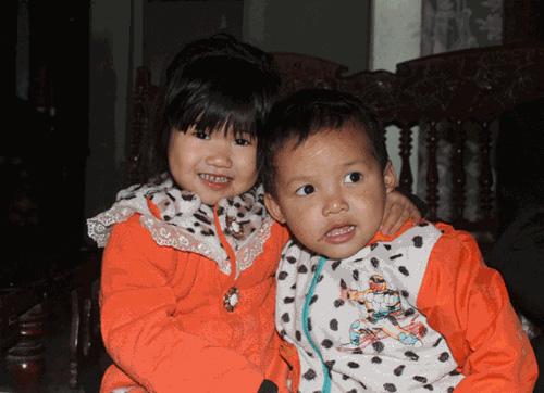 """Hai bé Thu và An đang được chị Thủy nuôi dưỡng (ảnh chụp tại nhà """"ông ngoại"""" - ông Nguyễn Văn Chế, bố chị Thủy)"""