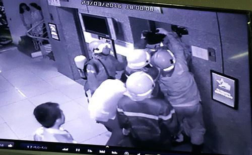 Cảnh sát dùng bơm thủy lực nạy cửa thang máy cứu 16 người mắc kẹt. Ảnh: Camera chung cư.