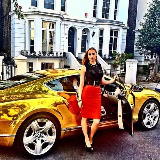Một tiểu thư diện váy đỏ sexy tạo dáng bên chiếc ôtô thể thao bọc vàng