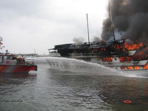 Tàu QN 6299 bốc cháy dữ dội, khiến hàng chục du khách nước ngoài hoảng loạn nhảy xuống nước thoát thân. Ảnh: Minh Cương.