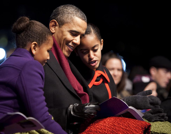 President Barack Obama and his daughters Sasha and Malia look at the program during the lighting of the National Christmas Tree in Washington December 1, 2011