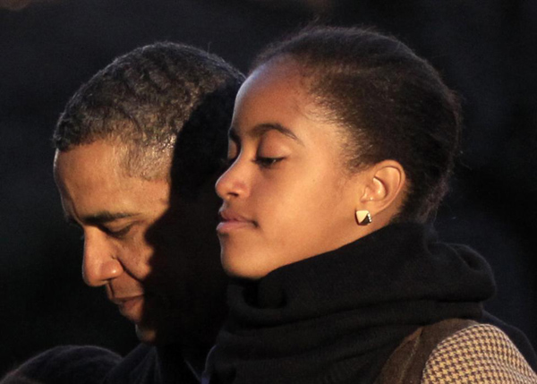 President Barack Obama and his daughter Malia walk towards the White House upon the first family's return from their vacation in Hawaii January 3, 2012.
