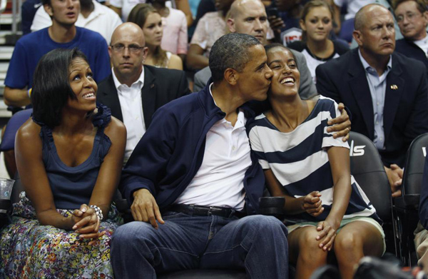 President Barack Obama kisses daughter Malia as first lady Michelle Obama looks up as they attend the Olympic men's exhibition basketball game between Team USA and Brazil in Washington July 16, 2012.