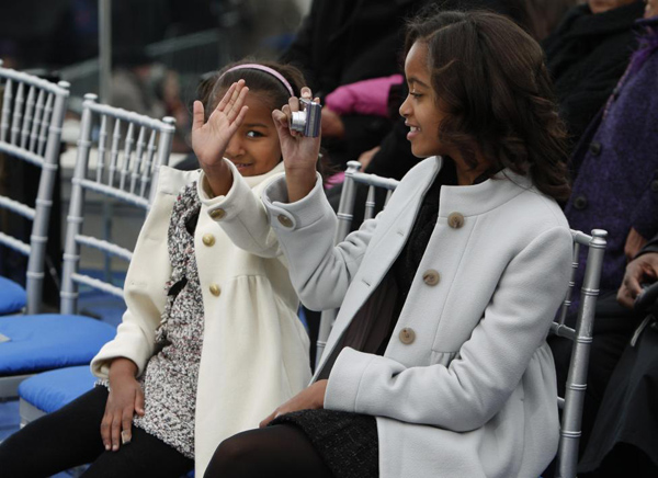 Sasha and Malia Obama, daughters of then President-elect Barack Obama, take pictures during the 'We Are One': Inaugural Celebration at the Lincoln Memorial in Washington January 18, 2009.