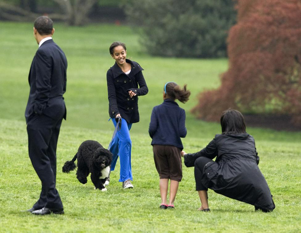 President Barack Obama presents the first family's new Portuguese Water Dog puppy, Bo, on the South Lawn with his family at the White House in Washington April 14, 2009. With Obama are daughters Malia and Sasha and first lady Michelle Obama.