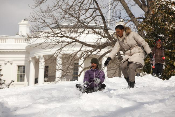 First Lady Michelle Obama sleds with daughters Malia and Sasha in the snow on the South Lawn of the White House in this handout photo taken in Washington, March 2, 2009 and later released by the White House.