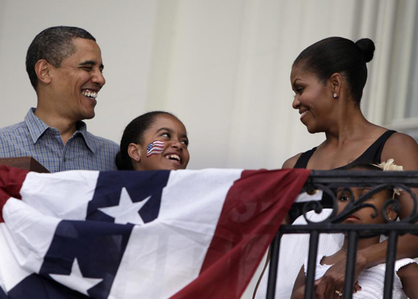 President Barack Obama smiles next to first lady Michelle Obama and their daughters Malia and Sasha during a Fourth of July celebration with military families on the South Lawn of the White House in Washington July 4, 2009.
