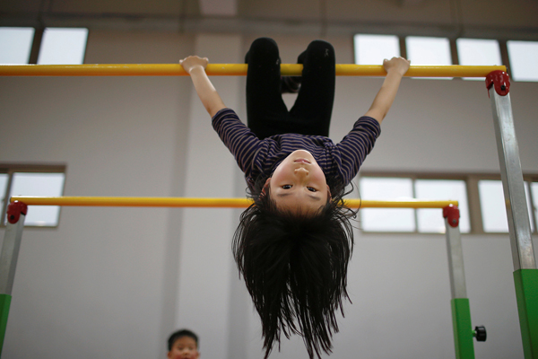 A girl practices during gymnastics lessons at the Shanghai Yangpu Youth Amateur Athletic School. 'We call it happy gymnastics,' said principal Zhu Zengxiang