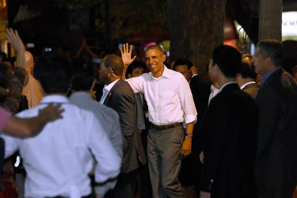 Ông Obama trong chiếc áo sơ mi trắng bước ra khỏi xe riêng. Thấy cả nghìn người dân reo hò chào đón, ông vẫy tay chào mọi người và tiến vào quán bún chả.