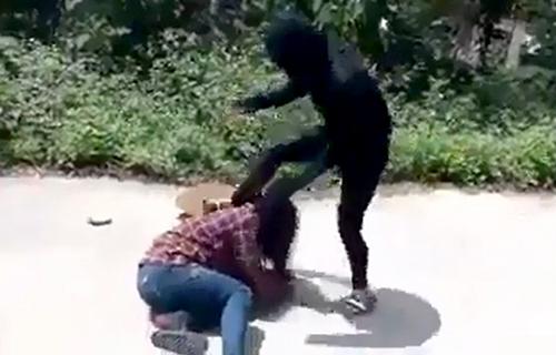 Cuối clip, cô gái mặc áo đen tiếp tục lao vào đá lên người nữ sinh lớp 12. Ảnh: Cắt từ clip.