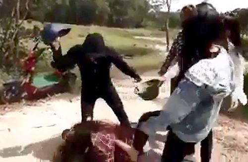 Nhóm 4 người cầm mũ cối, mũ bảo hiểm lao vào đánh, đấm đá túi bụi nữ sinh. Ảnh: Cắt từ clip.