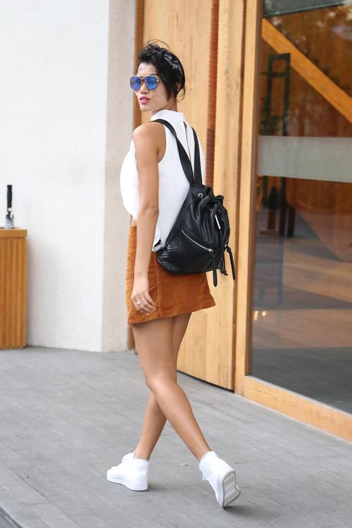 Trang Lạ trẻ trung với váy jean cài nút phối cùng các phụ kiện tôn nét năng động như ba lô và giày thể thao.