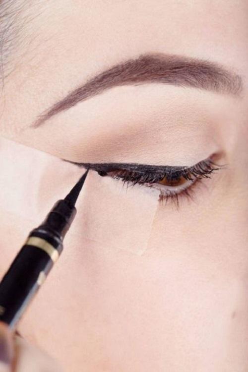 Kẻ mắt với băng dính Để có đường đuôi mắt hoàn hảo, bạn chỉ cần dán chéo băng dính thuận theo đường đuôi mắt và bóc ra sau khi kẻ xong.