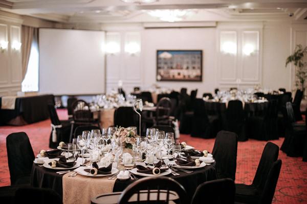 [Caption]Trong không gian tiệc tối, màu trắng lui lại nhường chỗ cho không gian sang trong pha chút kiêu kỳ của những chi tiết trang trí màu vàng đồng trên bàn tiệc.  Đặc biệt hơn cả là điểm nhấn của phụ kiện vải màu đen giúp tối đa hoá sự thanh lịch và kiểu cách của chủ đề 1920.