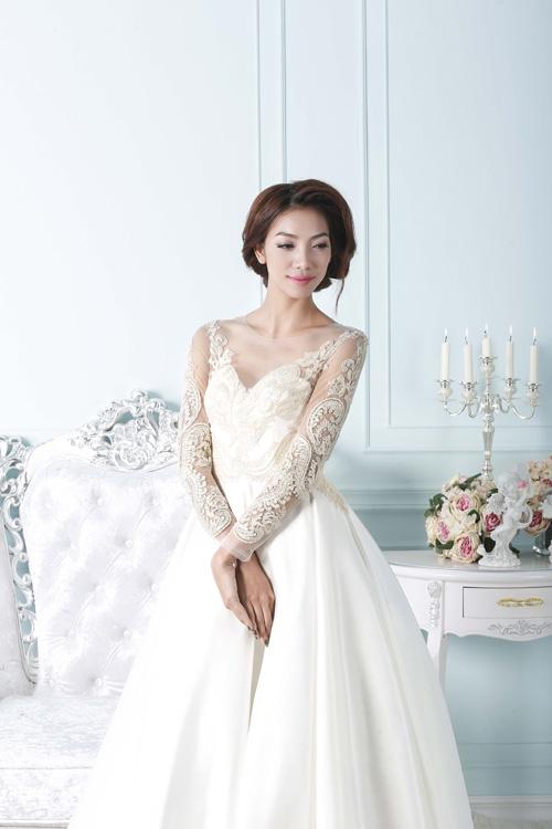 [Caption]Váy cưới trắng tinh khôi đính hoa 3D cầu kỳ với những cánh hoa rơi giúp cô dâu nổi bật trong đám cưới.  từ vải sheer mềm mại, xuyên thấu thêu ren tỉ mỉ. Xen lẫn họa tiết ren thêu nổi là chi tiết đính đá pha lê lấp lánh khiến bộ trang phục thêm bắt mắt.