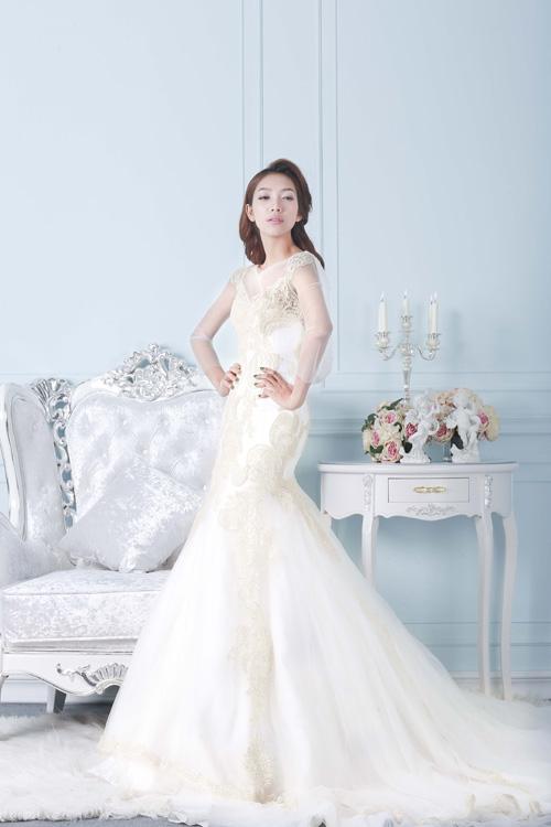 [Caption]Váy đuôi cá mang hơi hướng hiện đại, thanh lịch với những dải pha lê lấp lánh chạy dọc thân váy, họa tiết tinh tế nhấn ở viền cổ và tay.