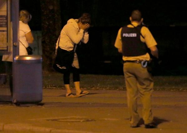 Một phụ nữ ôm mặt sau vụ xả súng ở trung tâm mua sắm. Ảnh: Reuters