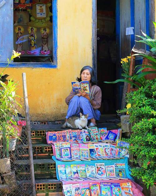 Hình ảnh thảnh thơi bình yên của bà lão bán truyện tranh cũ bên lề đường với chú mèo béo.