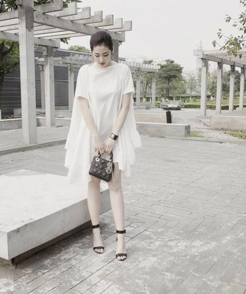 Người đẹp diện Blooming Dress màu trắng tinh khôi mix với giày sandanl cao gót màu đen thanh lịch.