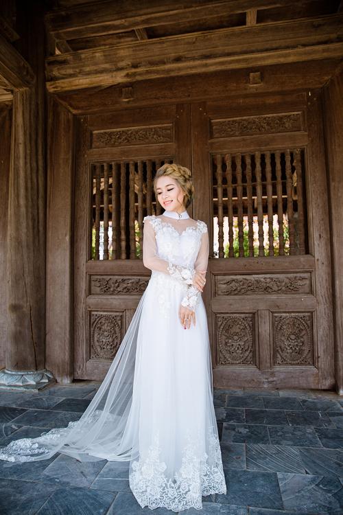 [Caption]Với chất liệu chủ yếu từ lưới voan và ren, áo dài cách tân mang dáng dấp gần giống như một chiếc váy dạ hội quyến rũ mà không mất đi vẻ trang trọng truyền thống.