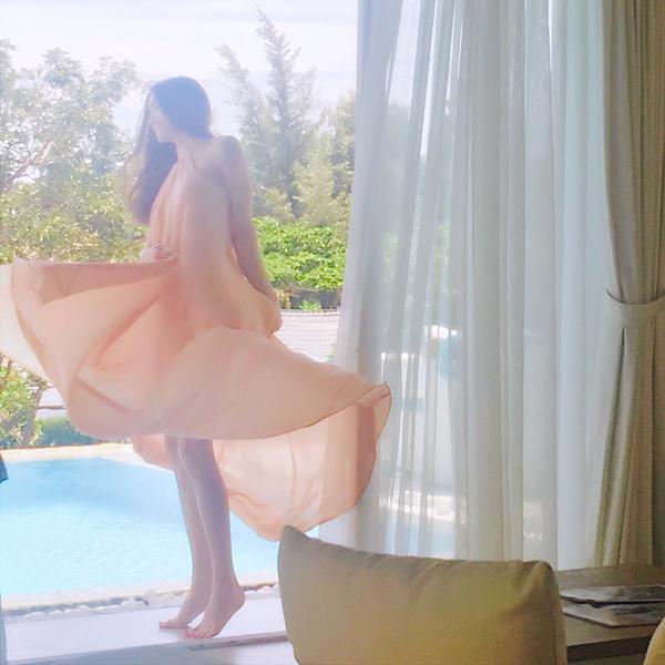 Hồ Ngọc Hà điệu đà thả dáng trong chiếc váy màu cam bên bể bơi: điệu lắm vì được đi chơi.