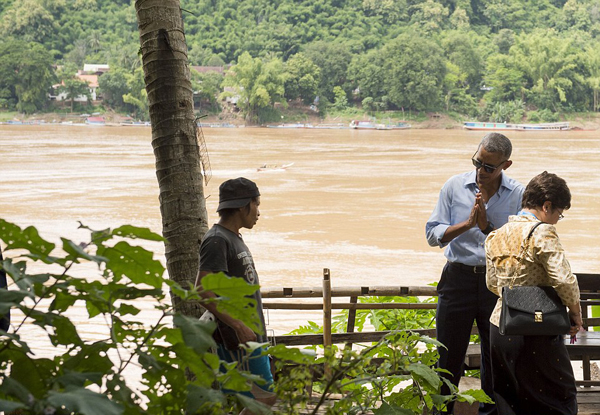 Pleased to meet you: US President Barack Obama gestures a traditional greeting to a local as he tours alongside the Mekong River in Luang Prabang