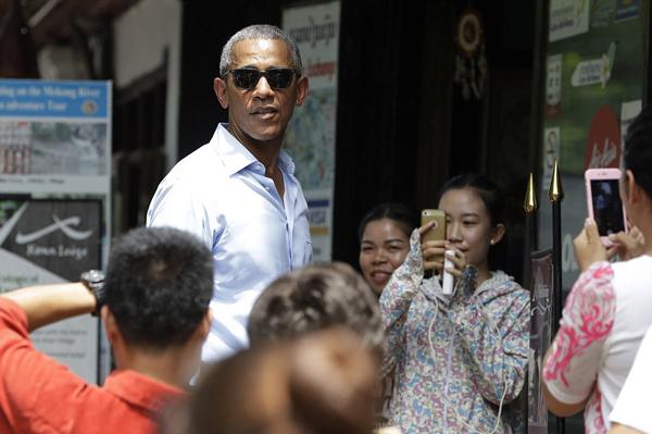 People take photos of U.S. President Barack Obama as he tours a shopping area near the Mekong River