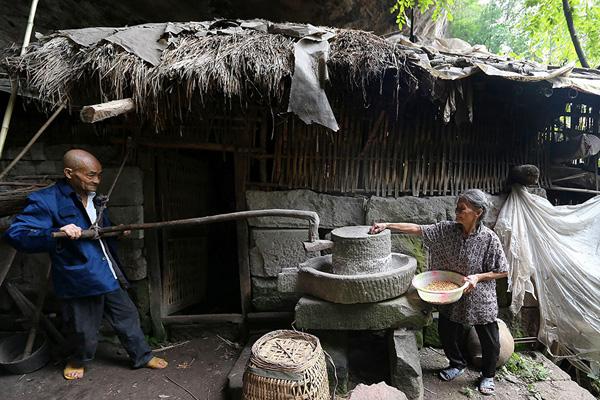 Cặp vợ chồng già đang cùng làm sữa đậu nành.