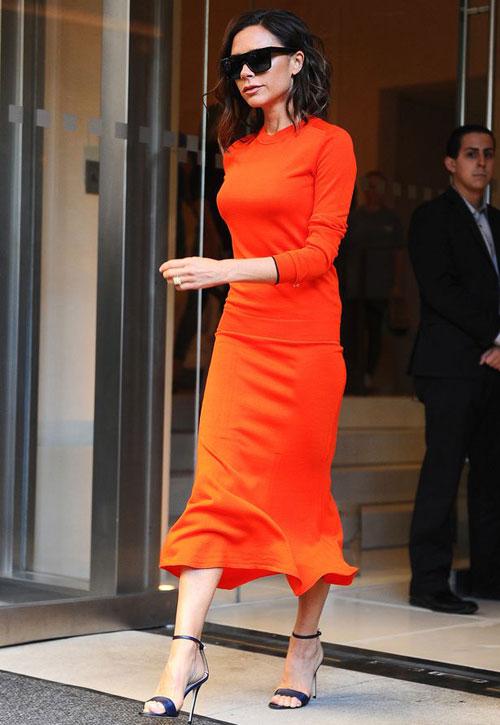 Một ngày sau buổi giới thiệu bộ sưu tập mới, Vic kiêu hãnh bước ra khỏi khách sạn trong bộ đầm màu cam tự thiết kế.