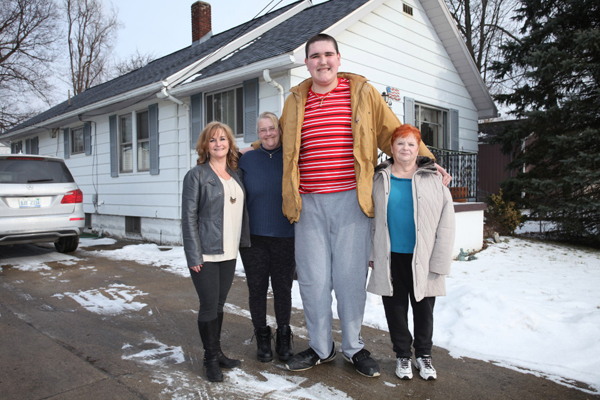 Broc poses with his family outside their home in Jackson, Michigan