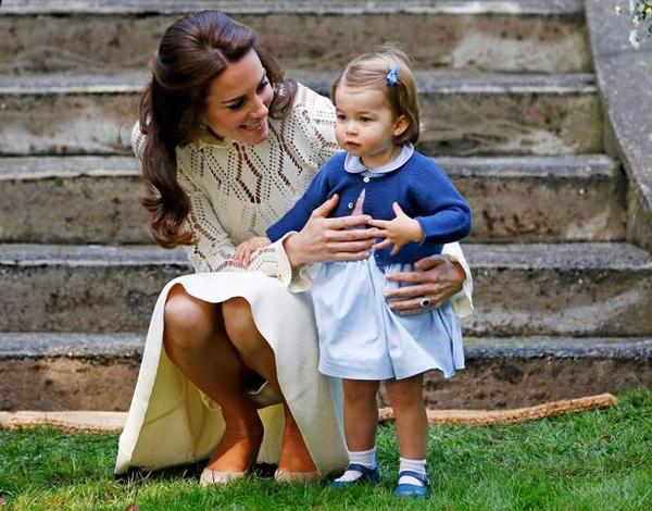 Kate xinh đẹp trong chiếc váy màu kem, bế con gái nhỏ trên tay khi cô bé được trao cho một quả bóng.