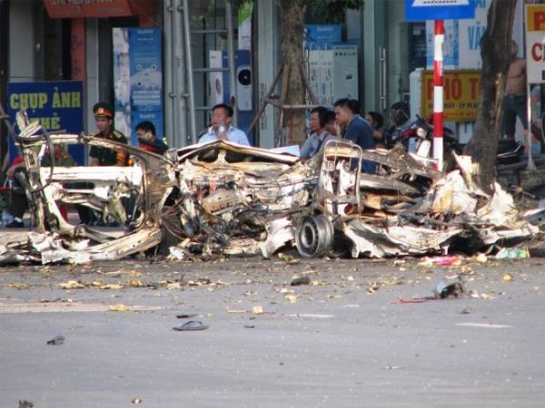 Sau vụ nổ, phần giữa và đuôi chiếc xe taxi 4 chỗ vỡ tung thành nhiều mảnh, các mảnh vỡ văng tung tóe bay hàng chục mét khắp đường.