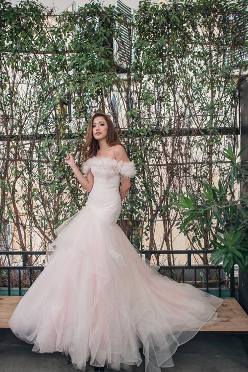 [Caption]Váy cưới trễ vai được làm mới bởi cách đính kết hạt ngọc trai công phu, tạo điểm nhấn ấn tượng trên bề mặt chất liệu.