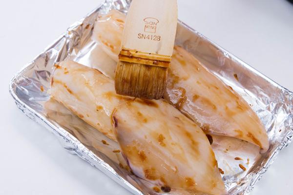 Bước 4: Làm nóng lò nướng ở nhiệt độ 180 độ C. Nhồi cơm vào trong con mực và quét lớp nước sốt teriyaki và tỏi bên ngoài.