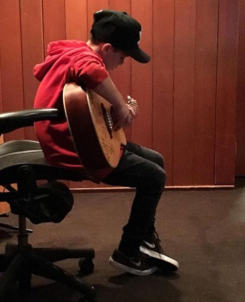 Cậu nhóc Cruz say sưa ôm đàn guitar, được dự đoán sẽ nối nghiệp ca hát của mẹ.