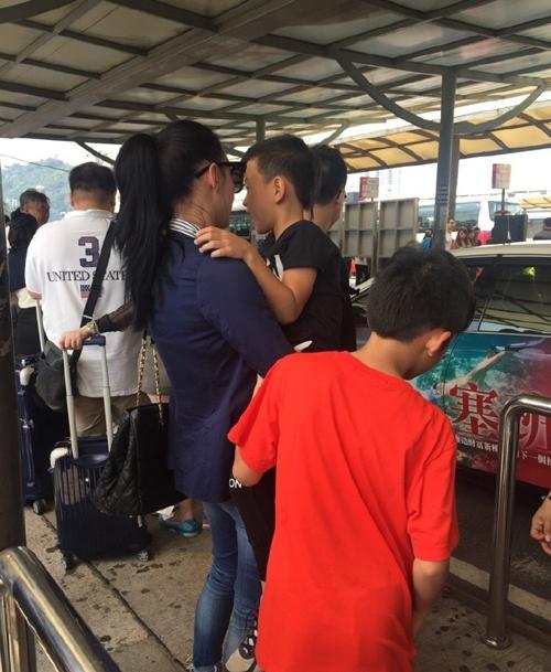 Paparazzi ghi lại hình ảnh của ba mẹ con Trương Bá Chi tại Macau hôm 5/11. Trong lúc chờ taxi tới, Bá Chi bế con trai thứ hai và cưng nựng cậu bé, trong khi Lucas đứng cạnh mẹ và tò mò nhìn ngó khắp nơi.