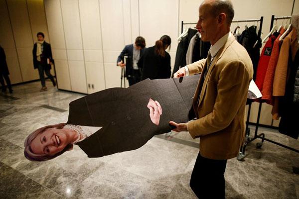 Một người đàn ông bê tấm hình cắt bà Clinton ra khởi địa điểm tổ chức sự kiện theo dõi bầu cử của Đại sứ quán Mỹ tại Seoul.