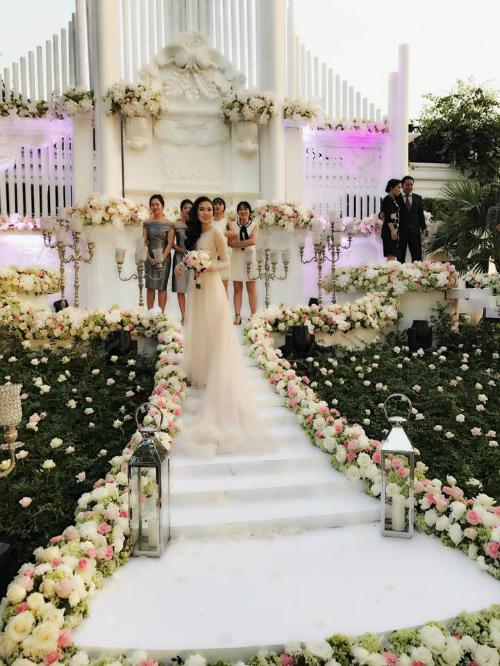 [Caption]Lễ cưới được tổ chức ngoài trời. Không gian trang trí ấn tượng như một nhà thờ với hai tông màu trắng - hồng chủ đạo.