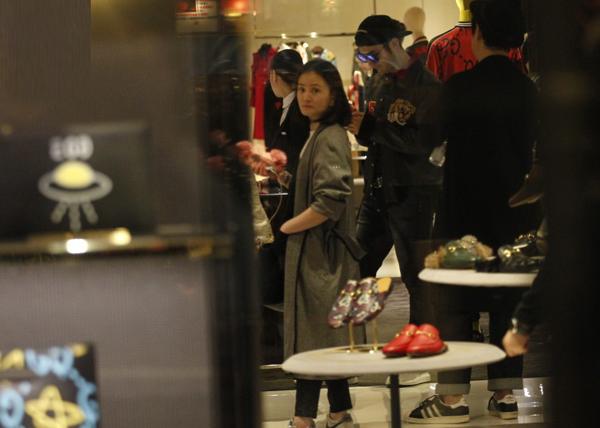 Trong khi vợ mải mê chọn đồ, Hiểu Minh đứng phía ngoài giết thời gian bằng cách xem điện thoại.