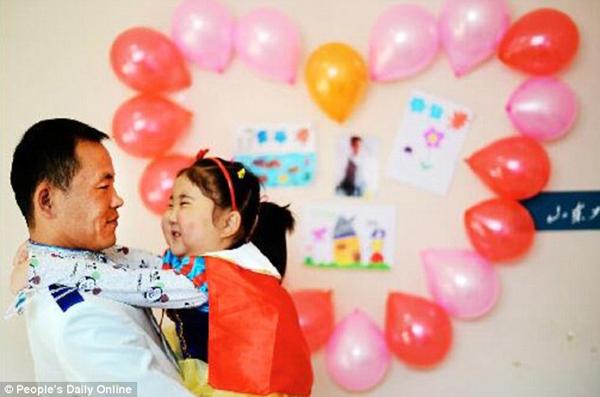 Cô bé Shi Haiqing ôm cổ bố cười tươi trong đám cưới. Ảnh: Peoples Daily Online