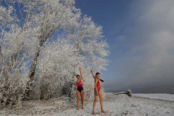 Cô bé 9 tuổi Nastya Usachyova khởi động cùng mẹ trước khi xuống bơi ở sông Yenisei, Krasnoyarsk.  Cô bé cho biết: Ban đầu cháu thấy lạnh nhưng rồi cũng quen.