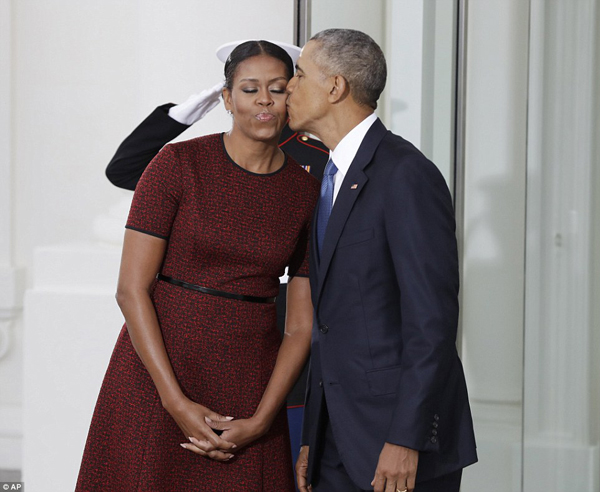 Before Mr Trump arrived at the White House, the Obama shared a sweet kiss - one of their last moments as president and first lady