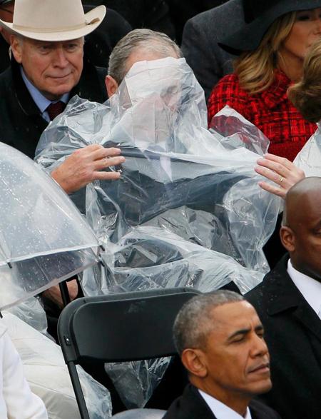Chiếc áo mưa bị thổi che cả mặt vị cựu tổng thống.
