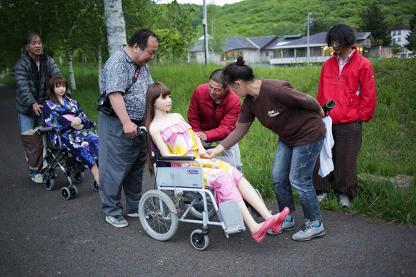 Senji shows Saori to local residents after a photo session with his friend at a lake in Nagan