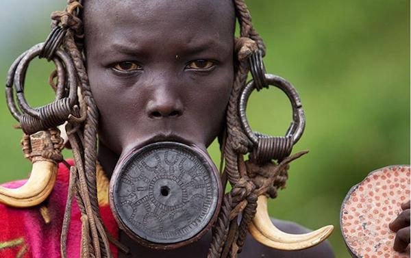 Các cô gái bộ tộc Mursi ở Ethiopia đặt một đĩa tròn ở môi dưới  để căng môi ra, và họ không ngừng tăng kích thước đĩa tròn làm bĩu môi. Phong tục này là một biểu tượng của vẻ đẹp và sự trưởng thành về mặt tình dục.