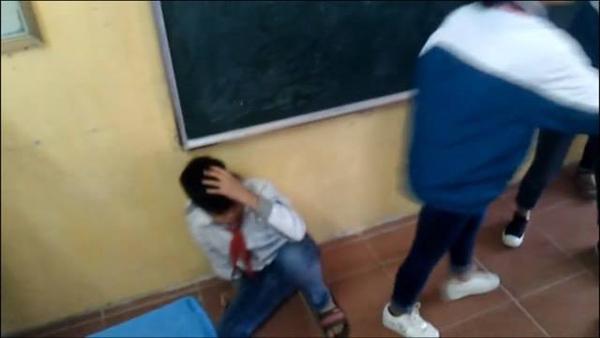 Thi ôm đầu sau khi bị bạn đánh. Ảnh cắt từ clip.