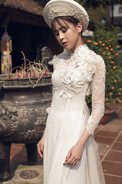 [Caption]Nữ người mẫu kín đáo, e ấp mà bay bổng khi khoác lên mình mẫu áo dài chất liệu mỏng nhẹ, bay bổng. Áo dài cưới màu trắng nhẹ nhàng nhưng cũng không kém phần sang trọng vì cách đính kết điệu đà.