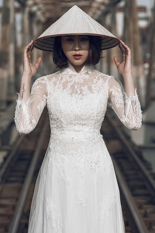 [Caption]Thân áo may bằng voan, trang trí bởi hoa văn ren cầu kỳ, gợi cảm giác nửa kín nửa hở để tôn nét quyến rũ của cô dâu. Tà áo có độ dài vừa phải, giúp cô dâu di chuyển dễ dàng trong ngày ăn hỏi.